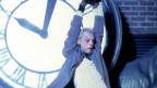 Ein Mann hängt an einer grossen Uhr.