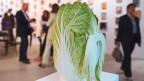 Ein Kohl mit einem Kohlschnauz ist auf einem Sockel als Kunstwerk präsentiert.