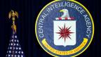 Das Amtssiegel der CIA und links daneben die US-Amerikanische Flagge