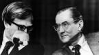 Schwarz-Weiss Foto zweier Männer. Einer hält die Hand vor den Mund – Es sieht so aus, als würde er dem Anderen ein Geheimnis zuflüstern.