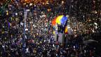 Zehntausende Menschen protestieren in Rumänien, inmnitten der Menschenmenge schwingt jemand die rumänische Flagge.