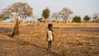 Ein kleiner somalischer Junge steht alleine in der Wüste.