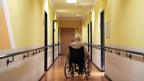 Ein alter Mann in einem Rollstuhl auf einem leeren Flur.