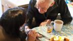 Alter Mann mit Spitex am Frühstückstisch.
