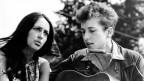 Schwarzweiss Foto von Joan Baez und Bob Dylan, die gemeinsam singen.