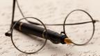 Auf einem handschriftlichen Brief liegt eine Brille und eine Füllfeder.