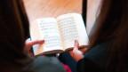 Rückenansicht von zwei Mädchen, die ein Kirchengesangsbuch halten.