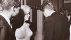 Schwarz-Weiss Foto einer einer Party. Mehere Leute stehen in einem Raum und unterhalten sich, mitten drin die einzige Frau.