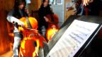Im Vordergrund: Ein Notenblatt. Im Hintergrund: Zwei Mädchen, die Cello spielen.