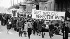 Schwarzweiss Foto einer Demonstration, vorne halten Menschen einen Banner «Gift und Gas – verbotene Waffen»