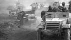 Schwarzweiss Foto von Panzern mit Soldaten drauf – um sie herum wirbelt Staub auf.