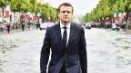 Macron läuft bei Regen auf der Strasse und schaut mit einem festen, ernsten Blick in die Kamera.