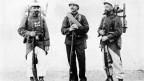 Schwarzweiss Foto von drei Soldaten in unterschiedlichen Uniformen