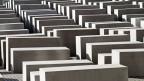 Viele hintereinander gereihte Betonklötze, die wie Särge aussehen, stehen auf einem Platz.