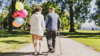 Ein älteres läuft Händchen haltend die Strasse runter, die Frau hält bunte Ballons in der Hand.