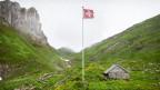 Eine hütte auf einer Alp und eine Schweizer Fahne daneben