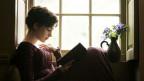 Eine im Empirestil gekleidete Frau sitzt am Fenster und liest ein Buch.