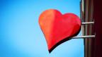 Rotes Herz als Schild vor blauem Himmel