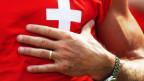 Ein Mann im Schweizer T-Shirt legt seine Hand auf die Brust.
