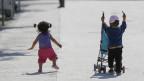 Zwei Kleinkinder laufen mit einem Kinderwagen durch das Flüchtlingslager