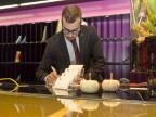 Ein Mann in Dienstkleidung beugt sich an einer Rezeption über Noitzbücher