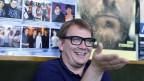 Sven Regener sitzt fröhlich gestikulierend vor einer bunten Plakatwand