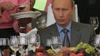 Putin sitzt an einem mit Wein, Früchten und Süssspeisen gedeckten Tisch und schaut konzentriert in die Ferne