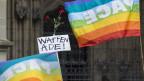 Regenbohnenfahnen, rote Nelken und ein Schlild mit der Aufschritt «Waffen Ade!» vor dem Berner Münster