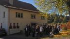 Ein grosses, freistehendes Haus, vor dem sich Menschen angesammelt haben