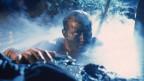 Ein Junge mit schlammverschmiertem Gesicht liegt in blauweissem Dunst im Schlamm und schaut konzentriert aus dem Bild