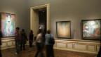 Menschen betrachten Gemälde in einer Ausstellung