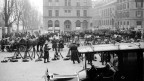 Schwarzweissfotographie vieler Soldaten und Pferdekutschen auf einem städtischen Platz