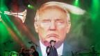 """Im Vordergrund die Rockband """"Fury In The Slaughterhouse"""" und im Hintergrund ein Bild von Donald Trump."""