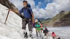 Ein Bergführer mit einer touristengruppe auf dem Getscher.
