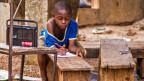 Ein Junge in Sierra Leone verfolgt den Schulunterricht aus dem Radio
