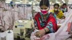 Frau bei der Arbeit in einer Textilfabrik in Bangladesh.