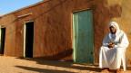 Ein Sudanese sitzt vor seinem Haus