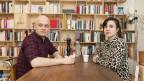 Ein Mann und eine Frau sitzen in einer Wohnstube am Tisch