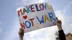 Auf einer Demo hält ein junger Mann ein Plakat in die Höhe mit der Aufschrift «Make Love Not War»