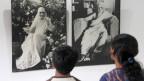 Zwei Personen stehen vor den Portraits der Auroville-Gründerin