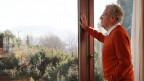 Älterer Herr in oragngenem Pullover schaut nachdenklich aus einem grossen Fenster