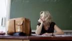 Lehrerin sieht müde aus dem Fenster.
