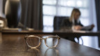 Eine Brille auf einem verlassenen Schreibtisch.