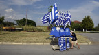 Ein Mann schiebt einen Wagen voll griechischer Flaggen.