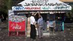 Zwei Männer vor einem Zeitungsstand in Griechenland.