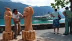 Ein Mann bearbeitet zwei Holzskulpturen