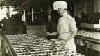 Ein altes Foto (ca. 1920) einer Frau, die in einer Schokoladenfabrik Schokostücke sortiert