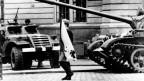 Ein junger Demonstrierender mit blutverschmierter Flagge der Tschechoslowakei neben einem sowjetischen Panzer