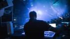 Ein Techno-DJ legt in einem Nachtclub auf.