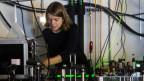 Eine junge Frau arbeitet in einem Labor an einem technischen Gerät